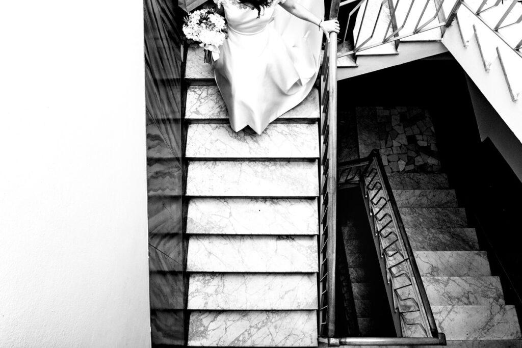 Foto in bianco e nero di sposa che scende le scale di casa